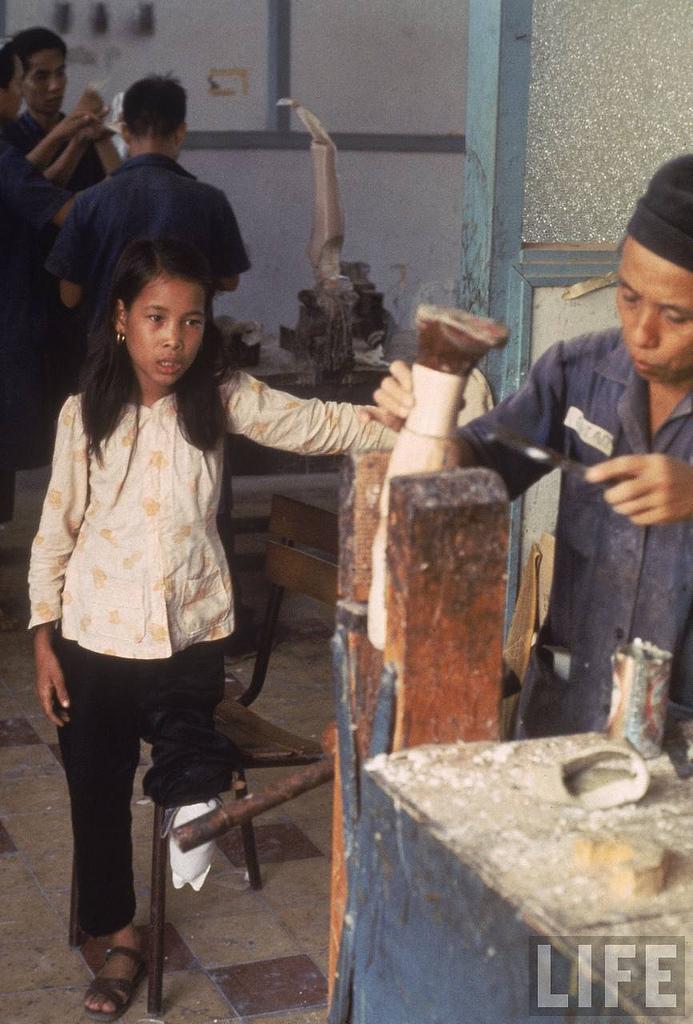 Bức ảnh cô Nguyễn Thị Tròn đang nhìn chiếc chân giả của mình được làm trên bìa tạp chí LIFE. Ảnh: Larry Burrows